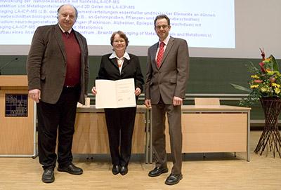Jürgen Grotemeyer (links) und Michael Desor (Fa. Waters, rechts) gratulieren Preisträgerin J. Sabine Becker zum Preis für Massenspektrometrie in den Biowissenschaften.