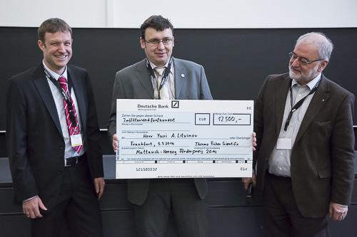 Yuri A. Litvinov (GSI Darmstadt) freut sich über einen richtig großen Scheck. Links Thomas Moehring (Thermo Fisher Scientific), rechts Michael Linscheid.